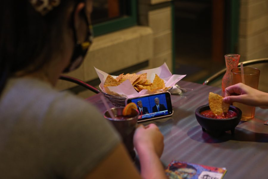 University of Iowa students Molly Fischer and Cassidy Beshel watch the second presidential debate on a phone while eating on Thursday, Oct. 22, 2020 at Casa Azul in Iowa City.