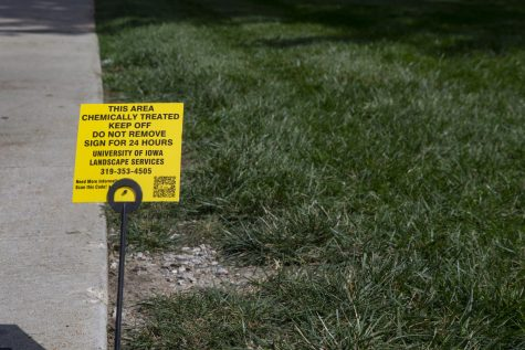 A sign warning students to stay off the grass sits on the Pentacrest on Sept. 4, 2019. Despite the warning about chemical treatment, some students continue to sit.