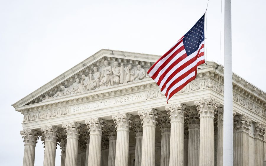 A picture of the supreme court, with the US flag waving in front of the phrase Equal Justice Under Law