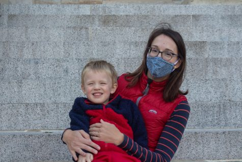 University of Iowa Lecturer of Earth and Environmental Sciences, Mary Kosloski, and her son, Felix, pose for a portrait at the Pentacrest on Oct. 16.