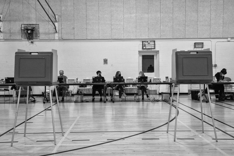 Precinct volunteers sit at tables behind voting stations at the Robert A. Lee Community Recreation Center in Iowa City on Tuesday, November 3, 2020. Few voters came as the evening approached 7:00 PM.
