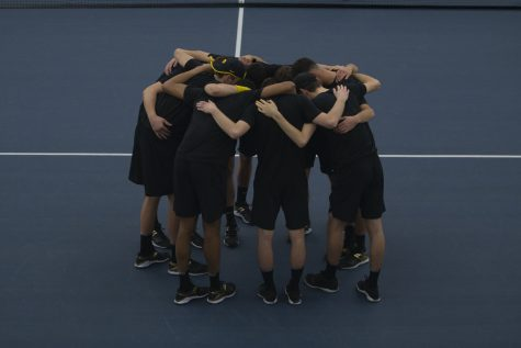 Iowa players huddle on the court before a men's tennis match between Iowa and Louisville on Friday, March 6, 2020 at The Hawkeye Tennis Recreation Complex. The Hawkeyes defeated the Cardinals 4-1.