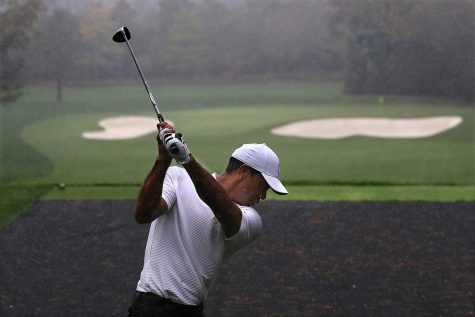 Defending champion Tiger Woods tees off in the rain on the par-3 4th hole during his practice round for the Masters at Augusta National Golf Club on Wednesday, Nov 11, 2020, in Augusta.