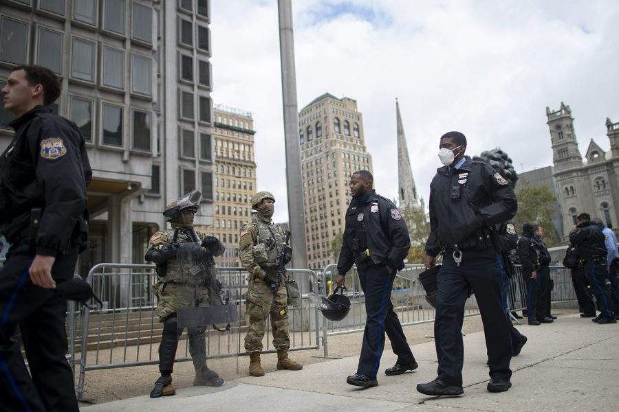 Police officers walk past as National Guard members monitor activity surrounding Philadelphia City Hall on October 30, 2020 in Philadelphia, Pennsylvania. In response to widespread unrest in the aftermath of Walter Wallace Jr.'s death, the National Guard arrived this afternoon to various locations throughout the city. The 27-year-old Walter Wallace Jr, a father of nine children, who Philadelphia police officers claimed was armed with a knife, was fatally shot by at least 14 total rounds.