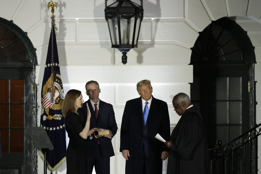 Judge+Amy+Coney+Barrett+is+sworn+in+as+the+Supreme+Court+associate+justice+by+Justice+Clarence+Thomas+as+her+husband+Jesse+Barrett+and+President+Donald+Trump+look+on+during+a+ceremony+on+the+South+Lawn+of+the+White+House+in+Washington%2C+D.C.+on+Oct.+26%2C+2020.+