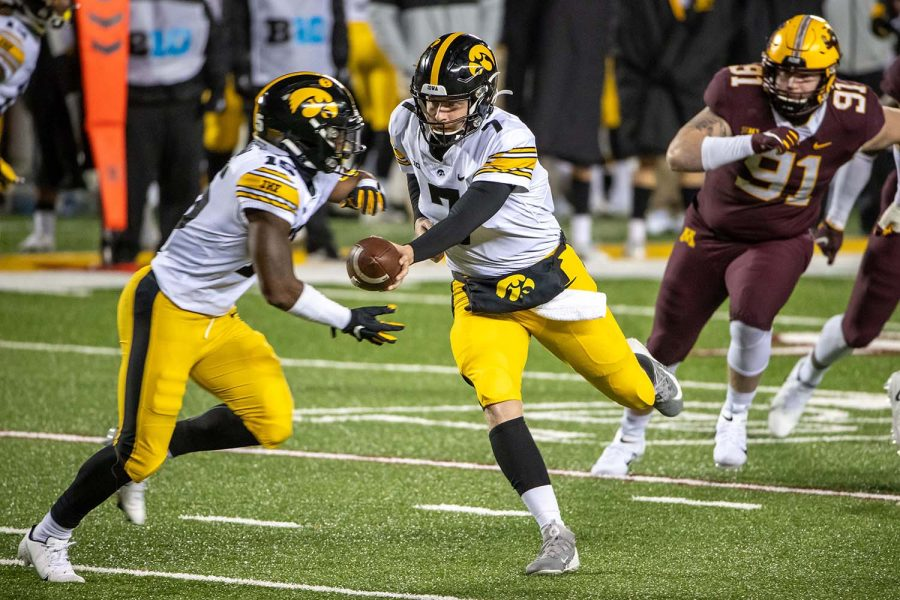 Nov 13, 2020; Minneapolis, Minnesota, USA; Iowa Hawkeyes quarterback Spencer Petras (7) hands the ball off to running back Tyler Goodson (15) in the second half against the Minnesota Golden Gophers at TCF Bank Stadium. (Jesse Johnson-USA TODAY)