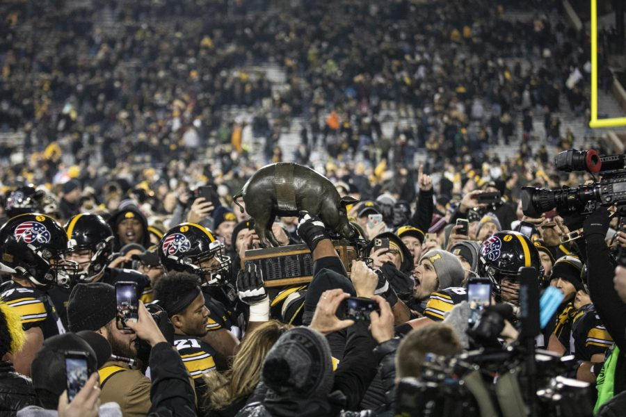 Iowa football players carry the Floyd of Rosedale trophy off the field after a football game between Iowa and Minnesota at Kinnick Stadium on Saturday, November 16, 2019. The Hawkeyes defeated the Gophers, 23-19.