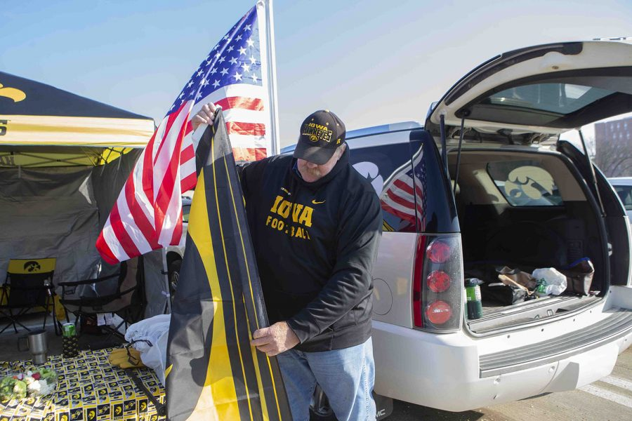 Ray Steffens folds up a Hawkeye flag in the Hancher Auditorium parking lot before the Iowa football game against No. 7-ranked Minnesota on Saturday, Nov. 16, 2019.