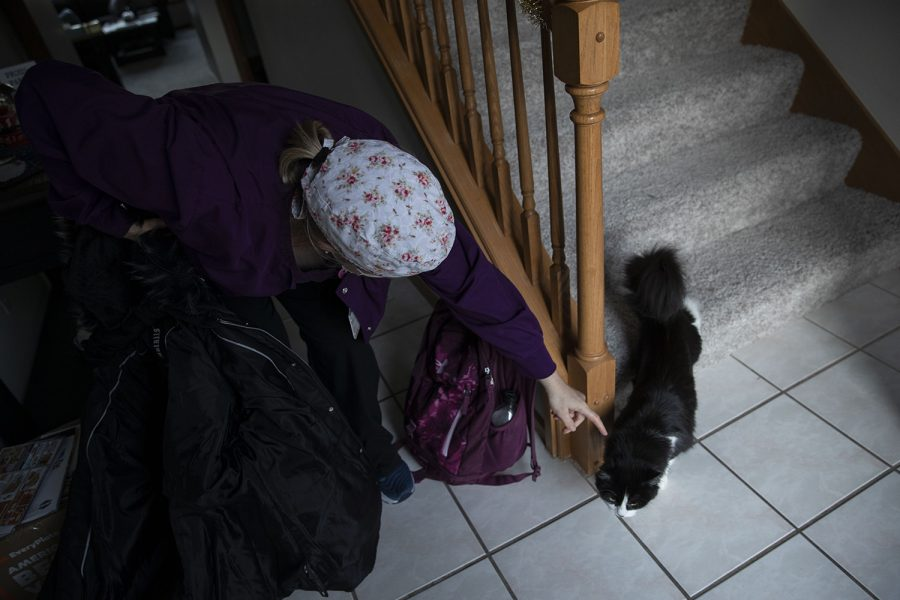 """Dawn Shannahan greets her cat at the door after returning home from work on Dec. 4, 2020. Shannahan works as an Educator in the in-patient Child and Adolescent Psychiatric Unit at UIHC. Shannahan enjoys spending time with her cat and family when not at work. """"I think I've probably been a little bit better about self-care within the last two to three months,"""" Shannahan said. """"Just realizing that… a couple months ago I realized this is really kicking my ass."""""""