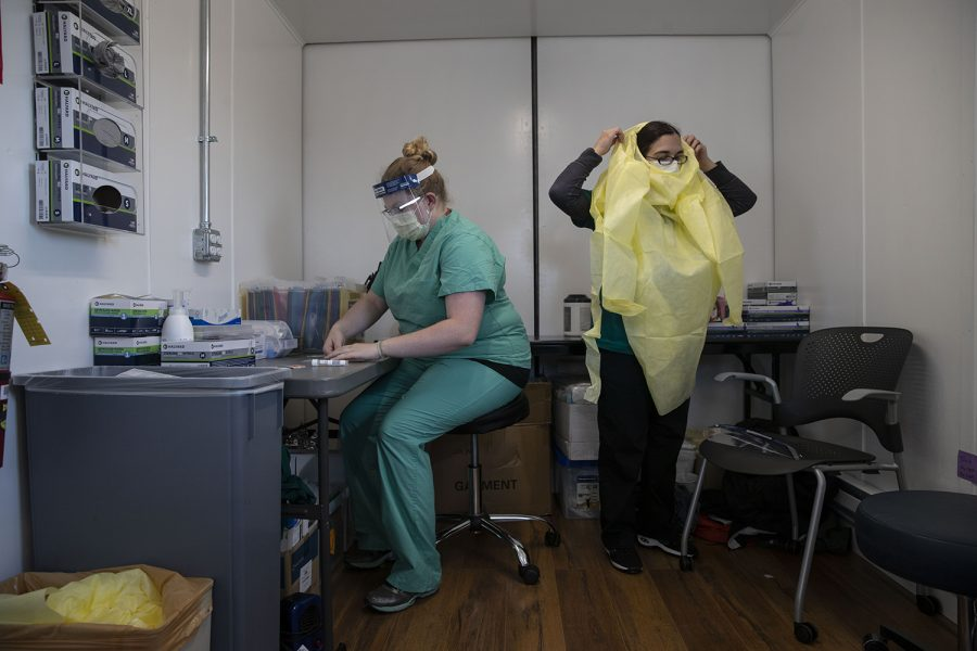 Medical Assistant Abbie Sura (right) puts on PPE while Tierney Maas preps more tests during a shift at a COVID testing site in the parking lot of UIHC Health Care - Urgent Care in Coralville on Thursday, Dec. 10, 2020. COVID cases are on the rise across the country again with a total of around 900 new cases reported in Johnson County between Nov. 25 - Dec. 8.
