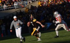 UI quarterback Drew Tate evades Ohio State defensive end Mike Kudla in the second half of the Hawkeye's victory over Ohio State on Oct. 16, 2004. Tate passed for 331 yards with three touchdowns, rushed for 24 yards with one touchdown and completed 26 of 39 passing attempts.