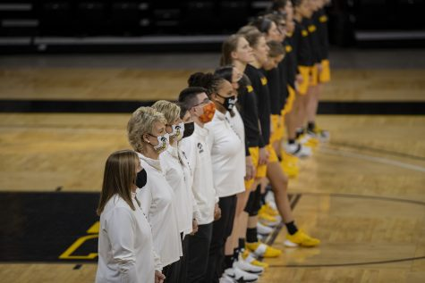 Iowa coaches and players stand during the national anthem before a women