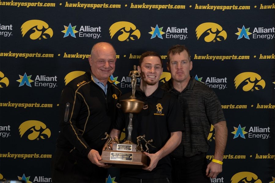 Iowa wrestler Spencer Lee holds the Hodge Trophy with his father Larry and Iowa Wrestling Coach Tom Brands at Kinnick Stadium on January 5 2021. The Hodge Trophy is awarded to the best wrestler in the nation and Lee is one of three Hawkeyes to win the award.