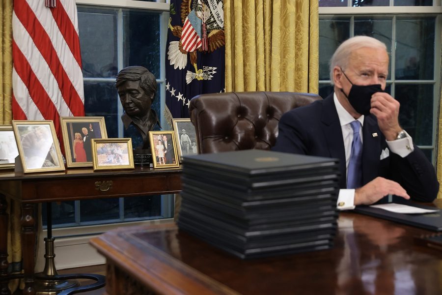 President Joe Biden prepares to sign a series of executive orders at the Resolute Desk in the Oval Office just hours after his inauguration on Wednesday, Jan. 20, 2021, in Washington, D.C. (Chip Somodevilla/Getty Images/TNS)