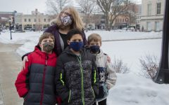 Julie Heidger and her children; Piers (left), Kaevion (middle), and Paul (right) pose for a portrait on Sunday, Jan. 24, 2021 on the Pentacrest at the University of Iowa. With no certainty when the pandemic will end, Heidger teachers her boys that their safe actions against COVID-19 can protect others.