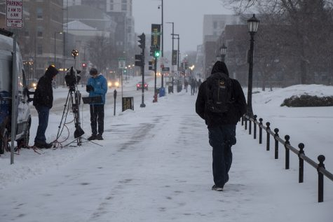 Students are seen walking to and from class in the snow while a reporter and cameraman set up equipment at the University of Iowa on Monday, Jan. 25, 2021. (Grace Smith/The Daily Iowan)