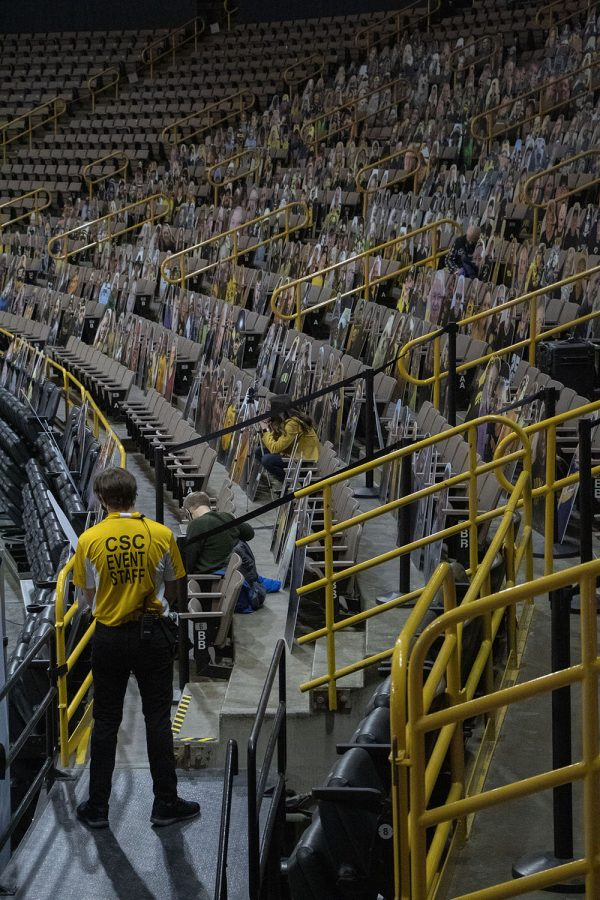 A staff member is seen amongst fan cutouts during the Iowa Women's Basketball game against Indiana at Carver Hawkeye Arena on Sunday, Feb. 7, 2021.