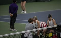 Doubles pair Alexa Noel (left) and Samantha Mannix (right) sit with a coach during the Iowa women's tennis meet v. Northwestern in the Hawkeye Tennis and Recreation Complex on Sunday, Feb. 14, 2021. Northwestern defeated Iowa with a score of 6-1.