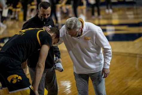 Iowa head coach Fran McCaffrey and Athletic Trainer Brad Floy check on forward Jack Nunge (2) after an apparent injury during the first half of a men's basketball game at the Crisler Center in Ann Arbor, Michigan on Thursday, February 25, 2021. McCaffrey said after the game that Nunge will undergo an MRI the following day. The Michigan Wolverines beat the Iowa Hawkeyes by a score of 79-57.