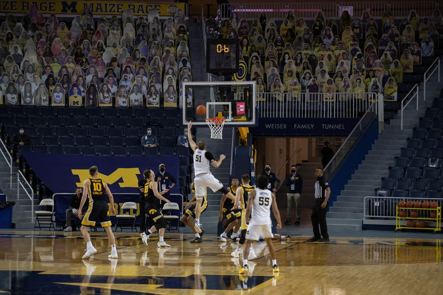 Michigan forward Austin Davis (51) tips the ball into the basket during the final second of the first half of a men's basketball game versus the Iowa Hawkeyes at the Crisler Center in Ann Arbor, Michigan on Thursday, February 25, 2021. The Wolverines took a 32-29 lead into the half and a strong second half performance led them to a 79-57 victory over the Iowa Hawkeyes.