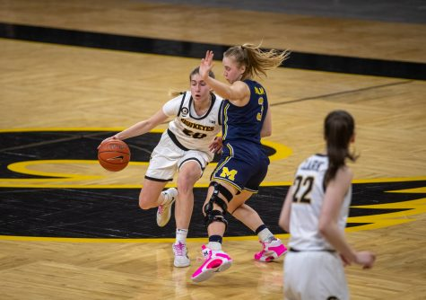 Iowa Guard Kate Martin dribbles the basketball past the logo. Michigan Guard Maddie Nolan shuffles to stay in front during a women