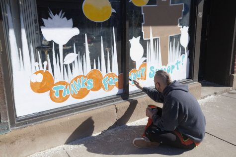 "Painter Todd Woodburn of Art n Devours paints a mural on a shop window downtown Iowa City, on Tuesday Feb. 23, 2021. ""A painting this ambitious takes about 6 hours to complete,"" Woodburn said."