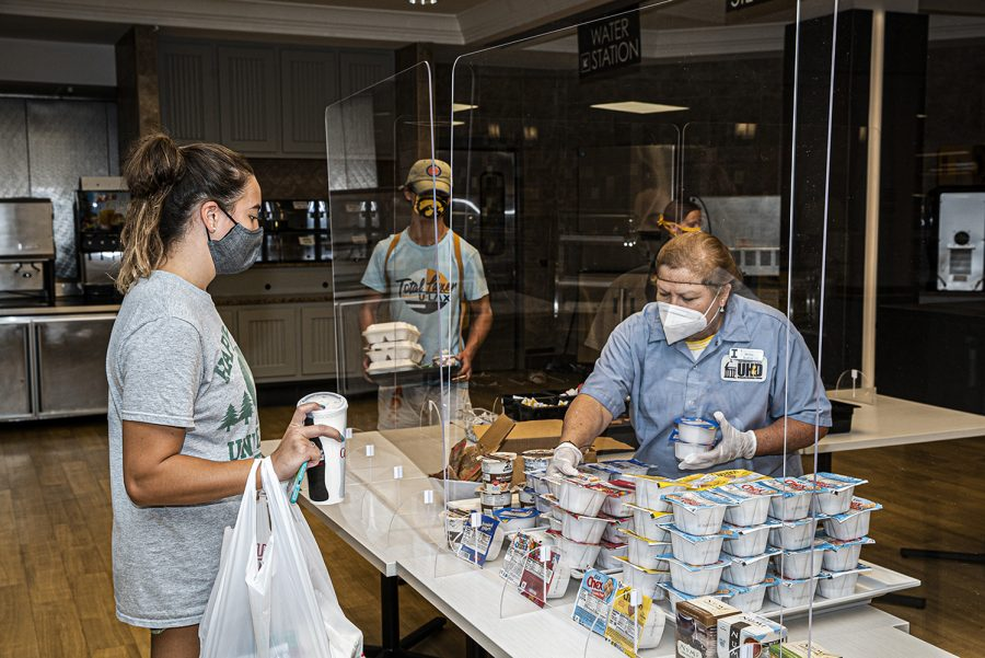 A Burge Marketplace worker serves a line of students on Monday, August 26th, 2020. Due to health and safety regulations as a means of preventing the spread of COVID-19, the dining hall process has been streamlined with an advanced registration process and a takeout meal process.