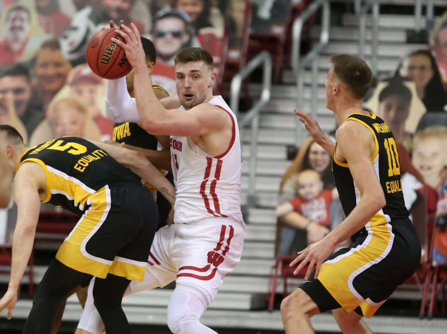 Feb 18, 2021; Madison, Wisconsin, USA; Wisconsin Badgers forward Micah Potter (11) fights for space among Iowa Hawkeyes defenders during the second half at the Kohl Center. Mandatory Credit: Mary Langenfeld-USA TODAY Sports