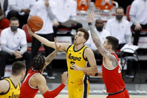 Feb 28, 2021; Columbus, Ohio, USA; Iowa Hawkeyes guard Jordan Bohannon (3) goes to the basket as Ohio State Buckeyes forward Kyle Young (25) defends during the first half at Value City Arena. Mandatory Credit: Joseph Maiorana-USA TODAY Sports