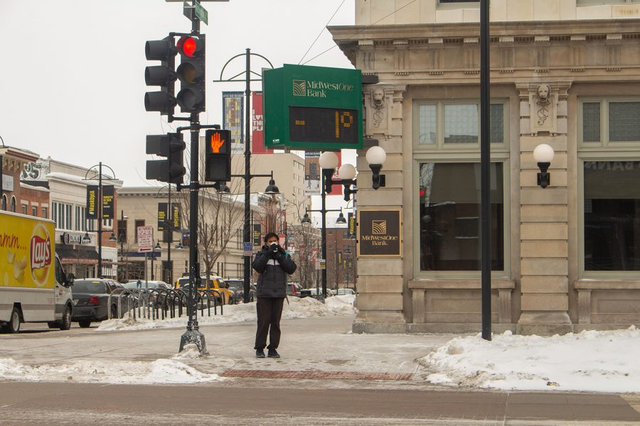 The Midwest One Bank sign at the corner of East Washington Street and South Clinton street reads negative one degrees Fahrenheit on Feb. 14 as a pedestrian is seen braving the weather as frostbite is possible within 10 minutes. The temperature on Sunday was expected to fall to negative 4 degrees with a wind chill of negative 24 degrees.