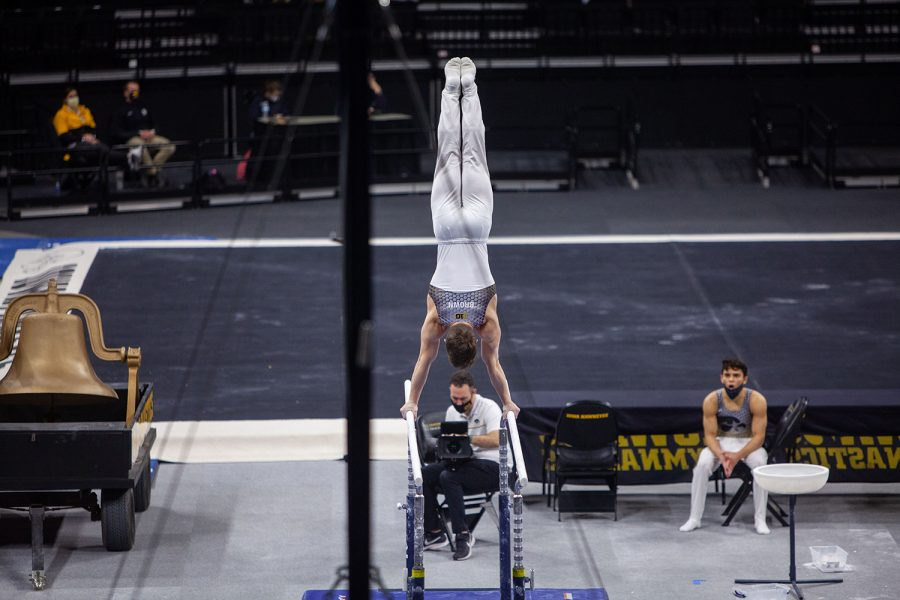 Iowa all-around Stewart Brown performs on the parallel bars on Saturday, Feb. 20, 2021 during the Iowa vs. Penn State men's gymnastics meet at Carver-Hawkeye Arena. Iowa defeated Penn State 398.850-393.550. Brown placed fifth overall on the parallel bars with a final score of 13.200.