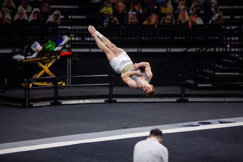 Iowa all-around Stewart Brown performs his floor routine on Saturday, Feb. 20, 2022 during the Iowa vs. Penn State men's gymnastics meet at Carver-Hawkeye Arena. Iowa defeated Penn State 398.850-393.550. Brown placed sixth in the overall floor results with a final score of 13.500.