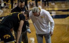 Iowa head coach Fran McCaffrey and Athletic Trainer Brad Floy check on forward Jack Nunge (2) after an apparent injury during the first half of a men's basketball game at the Crisler Center in Ann Arbor, Michigan on Thursday, February 25, 2021. Nunge was helped off the floor and to the locker room before later returning on crutches. McCaffrey said after the game that Nunge will undergo an MRI the following day. The Michigan Wolverines beat the Iowa Hawkeyes by a score of 79-57. (Jake Maish/The Daily Iowan)