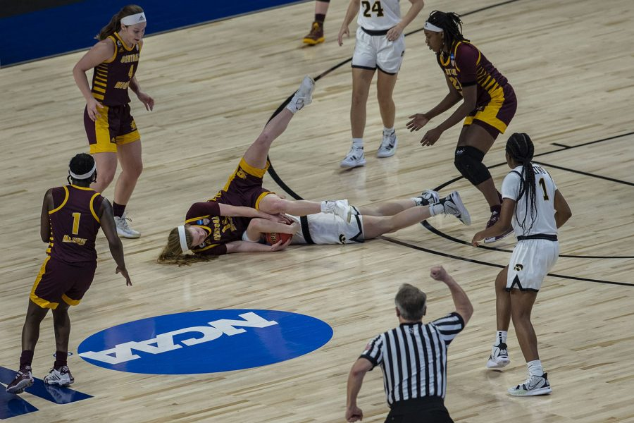 Iowa guard Kate Martin and Central Michigan guard Molly Davis fall while fighting for the ball during the first round of the NCAA women's basketball championship between Iowa and Central Michigan on Sunday, March 21, 2021 at the Alamodome in San Antonio, TX. The Hawkeyes defeated the Chippewas, 87-72. No. 5 Iowa will go on to play No. 4 Kentucky on Tuesday during the second round.