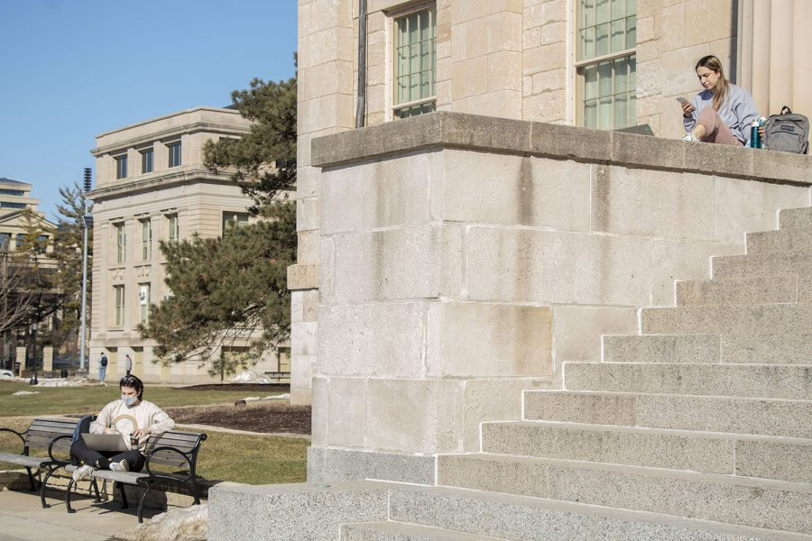 Two students, Nick Fitzpatrick (left) and Kourany Katzen (right) are seen on and near the Old Capitol Building on Tuesday, March 3, 2021, University of Iowa's instructional day.