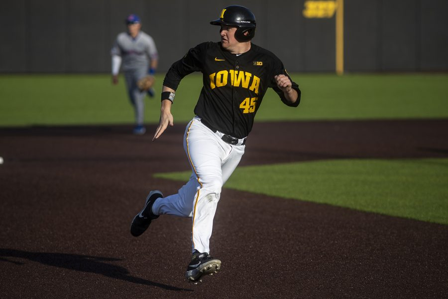 Iowa first baseman Peyton Williams watches where the ball is while racing to third base during a baseball game between the Iowa Hawkeyes and the Kansas Jayhawks on Tuesday, March 10, at Duane Banks Field. The Hawkeyes defeated the Jayhawks, 8-0.