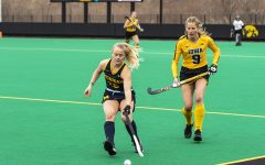 "Michigan Midfielder Sarah Pyrtek moves the ball upfield as Iowa Midfielder Sofie Stribos moves in during a field hockey game between Iowa and Michigan at Grant Field on Saturday, March 15, 2021. ""The Hawkeyes defeated the Wolverines, 2-1, in a shootout.""(Jeff Sigmund/Daily Iowan)"