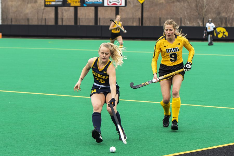 """Michigan Midfielder Sarah Pyrtek moves the ball upfield as Iowa Midfielder Sofie Stribos moves in during a field hockey game between Iowa and Michigan at Grant Field on Saturday, March 15, 2021. """"The Hawkeyes defeated the Wolverines, 2-1, in a shootout.""""(Jeff Sigmund/Daily Iowan)"""