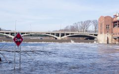 A sign warning of a dam upstream is seen in high waters in the Iowa River on March 8. (Ayrton Breckenridge/The Daily Iowan)