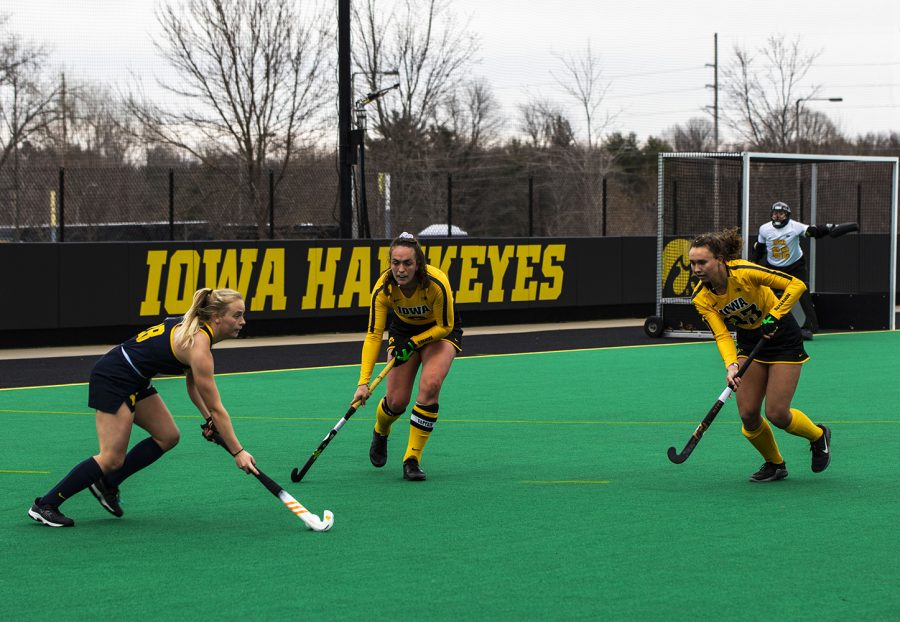 """Michigan Forward Sarah Pyrtek works to move the ball around Iowa defenders Anthe Nijziel (6) and Harper Dunne (23) during a field hockey game between Iowa and Michigan at Grant Field on Saturday, March 15, 2021. """"The Hawkeyes defeated the Wolverines, 2-1, in a shootout."""""""