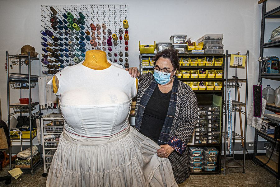 University of Iowa Costume Shop employee Barbara Croy demonstrates work on a dress designed for the Theatre Department's production of