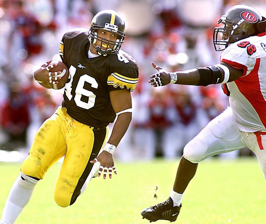 -  -Text: PC photo by Danny Wilcox Frazier --10/20/01-- Iowa's Ladell Betts flys past the arm of Indiana defender Dominique Smith during Iowa's 42-28 win over Indiana at Kinnich. Betts and Iowa's offense exploaded to lift the Hawkeyes to victory.  Title Iowa Football Betts