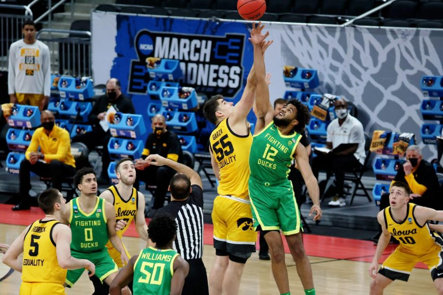 Mar 22, 2021; Indianapolis, Indiana, USA; Iowa Hawkeyes center Luka Garza (55) and Oregon Ducks guard LJ Figueroa (12) reach for the opening tipoff during the first half in the second round of the 2021 NCAA Tournament at Bankers Life Fieldhouse. Mandatory Credit: Trevor Ruszkowski-USA TODAY Sports