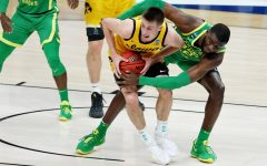 Mar 22, 2021; Indianapolis, Indiana, USA; Iowa Hawkeyes guard Joe Wieskamp (10) holds the ball while defended by Oregon Ducks center Franck Kepnang (22) during the first half in the second round of the 2021 NCAA Tournament at Bankers Life Fieldhouse. Mandatory Credit: Trevor Ruszkowski-USA TODAY Sports