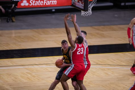 Iowa Center Luka Garza (55) goes up for a shot while heavily defended during a men's basketball game between the Iowa Hawkeyes and the Ohio State Buckeyes at Carver-Hawkeye Arena on Thursday, Feb. 4, 2021. The Buckeyes defeated the Hawkeyes in a close game, 89-85.