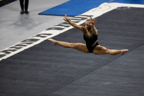 Iowa's Lauren Guerin is seen doing a jump during her floor routine at a women's gymnastics meet between the Iowa Gym-Hawks and the Minnesota Golden Gophers at Carver-Hawkeye Arena on Saturday, Feb. 6, 2021. The Hawks defeated the Gophers, 196.800-196.375.