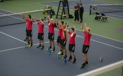 Iowa players chant and cheer on Will Davies during his singles match at the Iowa Men's tennis meet v. Wisconsin in the Hawkeye Tennis and Recreation Complex on Friday, March. 12, 2021. The Hawkeyes defeated the Badgers 5-2.