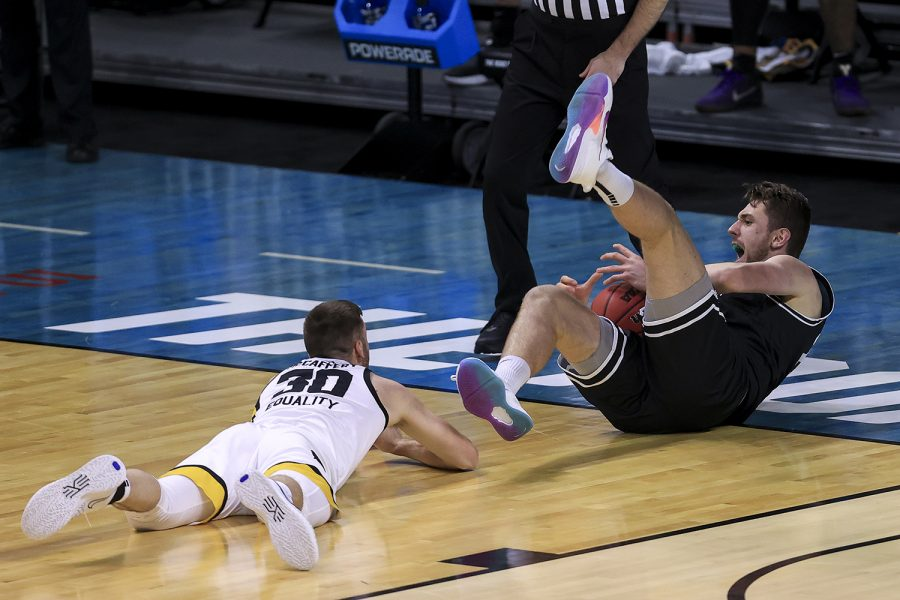 Mar 20, 2021; Indianapolis, IN, USA; Grand Canyon Antelopes center Alessandro Lever (25) is tripped by Iowa Hawkeyes guard Connor McCaffery (30) during the first round of the 2021 NCAA Tournament at Indiana Farmers Coliseum.
