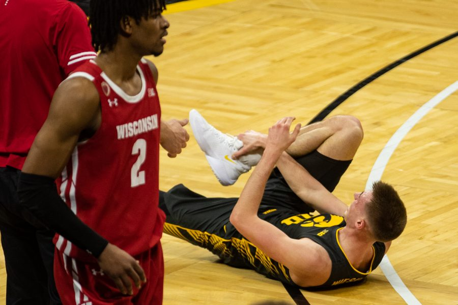 Iowa's Joe Wieskamp lays injured on the ground during a men's basketball game between Iowa and Wisconsin at Carver-Hawkeye Arena on Sunday, March 7, 2021. The Hawkeyes, celebrating senior day, defeated the Badgers, 77-73. (Shivansh Ahuja/The Daily Iowan)