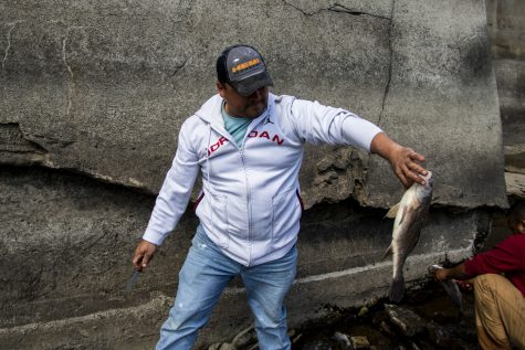 Adam Escavar shows his biggest catch so far on Sunday, April 18, 2021. Escavar spent the morning fishing below the Burlington Street dam. Escavar says they came down to fish for lunch.